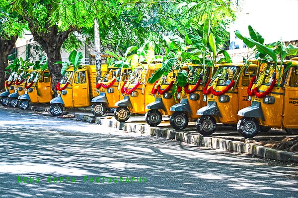 Decorated yellow transportation autos in Bangalore, India