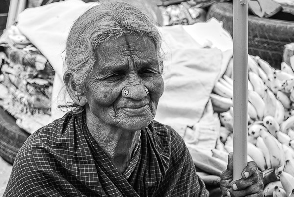 A black & white portrait of an old lady in a market