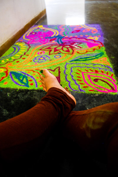 Colorful Rangoli and the feet of artist